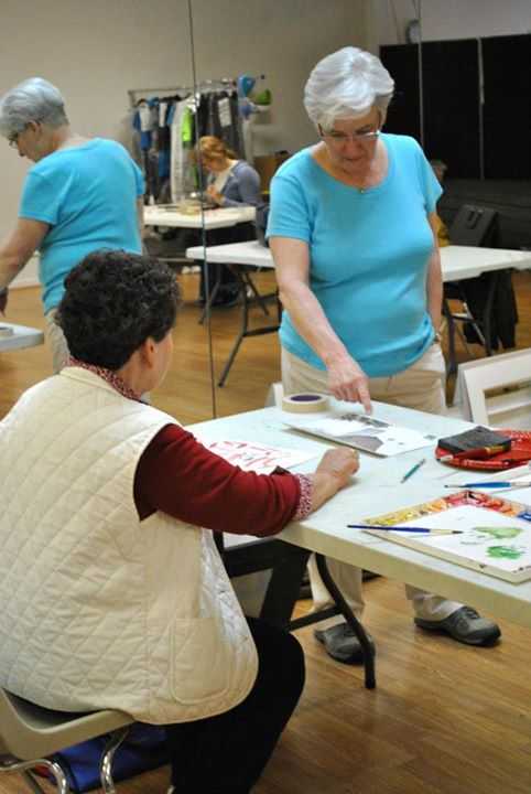 Adult Watercolor instructor Jeanne McLeish works with a student